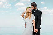 affectionate wedding couple in suit and white dress holding hands and looking at each other on beach