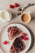 top view of arrangement of cup of coffee and sweet pastry with raspberries on plate on light surface