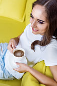 high angle view of beautiful smiling girl holding cup of coffee and sitting on couch