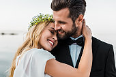 affectionate wedding couple in suit and white dress hugging on beach
