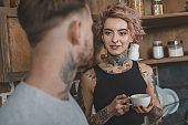 beautiful tattooed couple drinking coffee together at morning