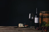close-up view of glass, bottle and barrel of wine with cheese and grapes on black