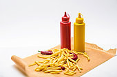 close-up shot of delicious french fries with pepper, ketchup and mustard on white