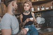 young tattooed couple drinking coffee together at morning