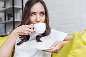 beautiful pensive brunette girl drinking coffee and looking away at home