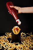 cropped shot of woman pouring ketchup on french fries isolated on black