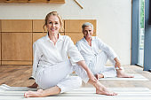 happy senior couple practicing yoga and smiling at camera