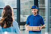Woman receiving stack of pizzas in boxes from courier