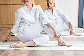 cropped shot of sporty senior couple sitting in yoga mats and practicing yoga