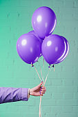 cropped shot of woman holding purple helium balloons