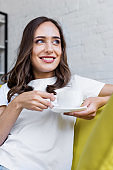 happy young woman holding cup of coffee and looking away at home