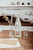 selective focus of branch with leaves in vase and bottle of water at wooden table in kitchen