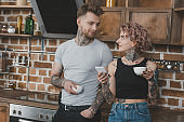 young tattooed couple drinking coffee and using smartphone in kitchen at morning