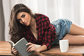seductive girl in checkered shirt holding book and looking at camera