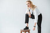 attractive blonde model with glass of whiskey posing with stool, isolated on grey