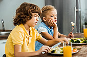 side view of unhappy little kids eating vegetables