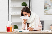 sick young businesswoman sneezing with paper napkin at workplace