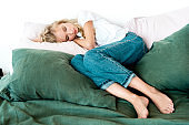 young woman in casual clothing sleeping on pillows on bed at home