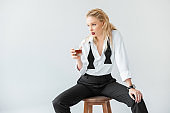 fashionable blonde woman with glass of whiskey sitting on stool, isolated on grey