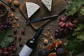 top view of wine bottle with blank label and delicious cheese on wooden table