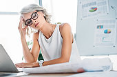 beautiful tired businesswoman looking at documents in office