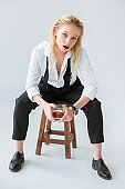 attractive fashionable model with glass of whiskey sitting on stool on grey