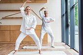 sporty senior couple practicing yoga on yoga mats