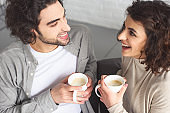 high angle view of young laughing couple drinking coffee at home