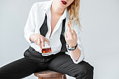 cropped view of elegant woman with glass of whiskey sitting on stool and showing middle finger, isolated on grey