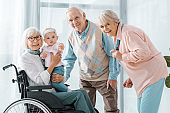happy senior people with toddler in nursing home