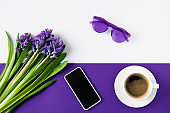 top view of bouquet of purple hyacinth flowers and smartphone on table