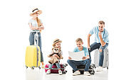 Happy family sitting on baggage and looking on map isolated on white