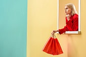 pensive fashionable woman in red clothing with red shopping bags looking out decorative window