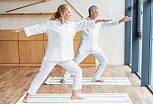 Full length view of elderly couple practicing yoga and performing warrior yoga pose together