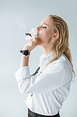 beautiful fashionable young woman smoking cigar isolated on grey