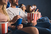 partial view of emotinal multiethnic friends with popcorn watching film together in movie theater