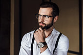 fashionable thoughtful man in trendy eyeglasses