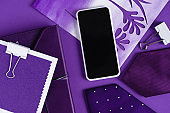 top view of workspace in purple color shades with smartpohone and supplies