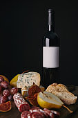 bottle of wine with blank label and delicious snacks on black