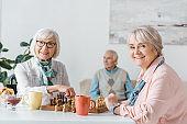 senior women playing chess and drinking coffee while senior man sitting on sofa