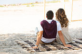 back view of couple resting on blanket on sandy beach