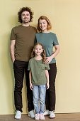 full length view of happy family with one child standing together and smiling at camera