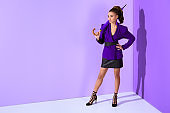 fashionable mulatto girl posing in purple jacket with umbrella at ultra violet wall
