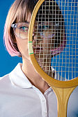 portrait of tennis player covering half of face with tennis racket isolated on blue