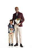 Yong african man and kid standing with flowers