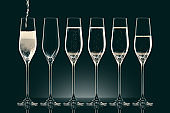 pouring champagne into six transparent glasses on black