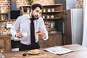 handsome loner businessman talking by smartphone while having breakfast at kitchen