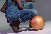 man crouching with golden basketball ball on grey