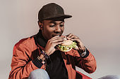 man eating hamburger isolated on grey