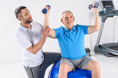 rehabilitation therapist assisting senior man exercising with dumbbells on fitness ball on grey backdrop
